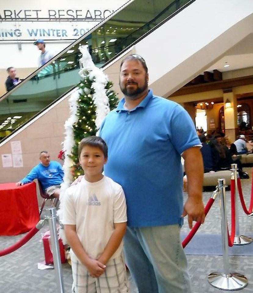 Photo - Edmond's Jeff Lampe takes time to have fun Friday with his son, Zach, at Quail Springs Mall. PHOTOS BY KEVAN GOFF-PARKER, FOR THE OKLAHOMAN