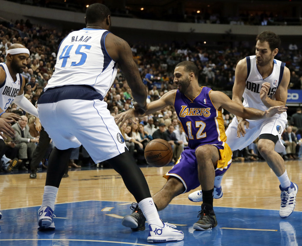 Photo - Dallas Mavericks' Vince Carter, left, DeJuan Blair (45) and Jose Calderon, right, combine to strip the ball away fro Los Angeles Lakers' Kendall Marshall (12) in the first half of an NBA basketball game, Tuesday, Jan. 7, 2014, in Dallas. (AP Photo/Tony Gutierrez)