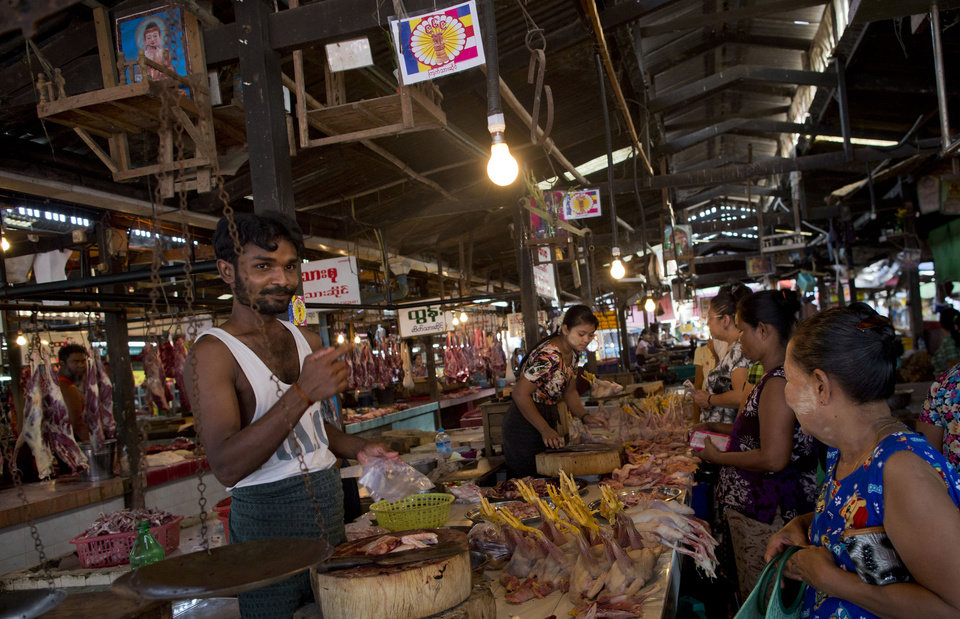 In this photo taken on April 4, 2013, customers buy meat from vendors displaying 969 signs at Kyimyindaing market in Yangon, Myanmar. (AP Photo/Gemunu Amarasinghe)