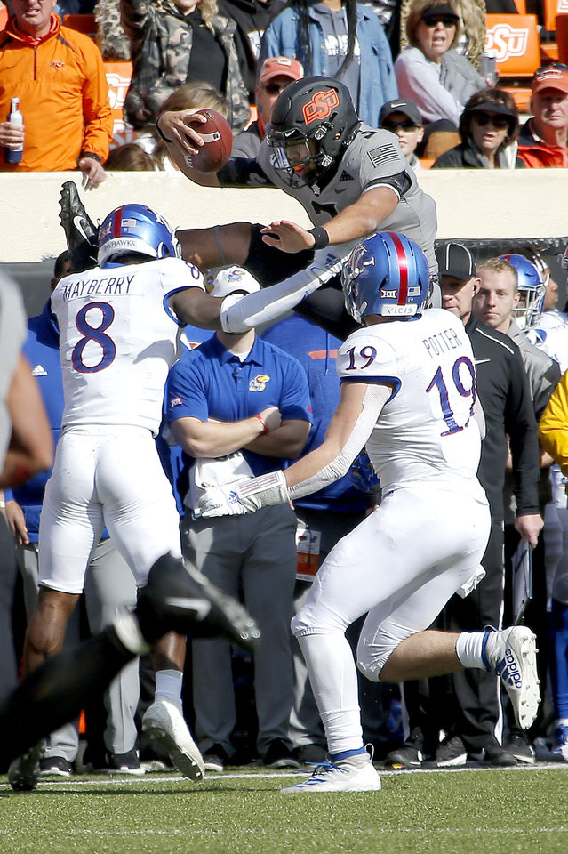 Photo - Oklahoma State's Spencer Sanders (3) leaps as Kansas's Kyle Mayberry (8) and Gavin Potter (19) defend in the first quarter during the college football game between the Oklahoma State University Cowboys and the Kansas Jayhawks at Boone Pickens Stadium in Stillwater, Okla., Saturday, Nov. 16, 2019. OSU won 31-13. [Sarah Phipps/The Oklahoman]