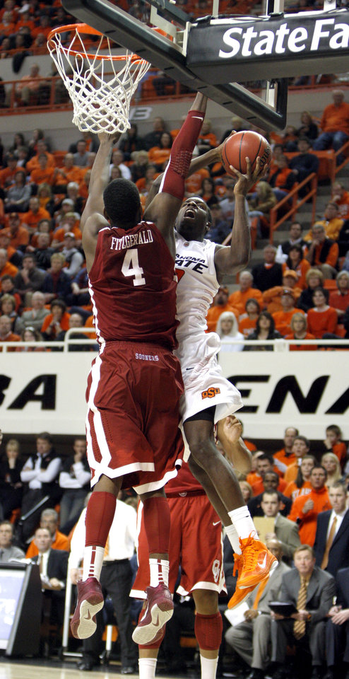 Photo - Oklahoma State's Jean-Paul Olukemi (0) shoots over Oklahoma's Andrew Fitzgerald (4) during the Bedlam men's college basketball game between the University of Oklahoma Sooners and Oklahoma State University Cowboys at Gallagher-Iba Arena in Stillwater, Okla., Saturday, February, 5, 2011. Photo by Sarah Phipps, The Oklahoman