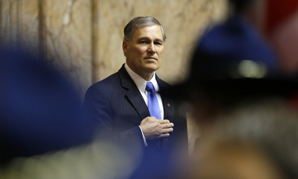 Photo - Gov. Jay Inslee stands with his hand over his heart as he watches a Washington State Patrol honor guard bring in the U.S. flag to a joint session of the Legislature, Wednesday, Jan. 16, 2013, in Olympia, Wash. shortly after Inslee was sworn in as governor. (AP Photo/Ted S. Warren)