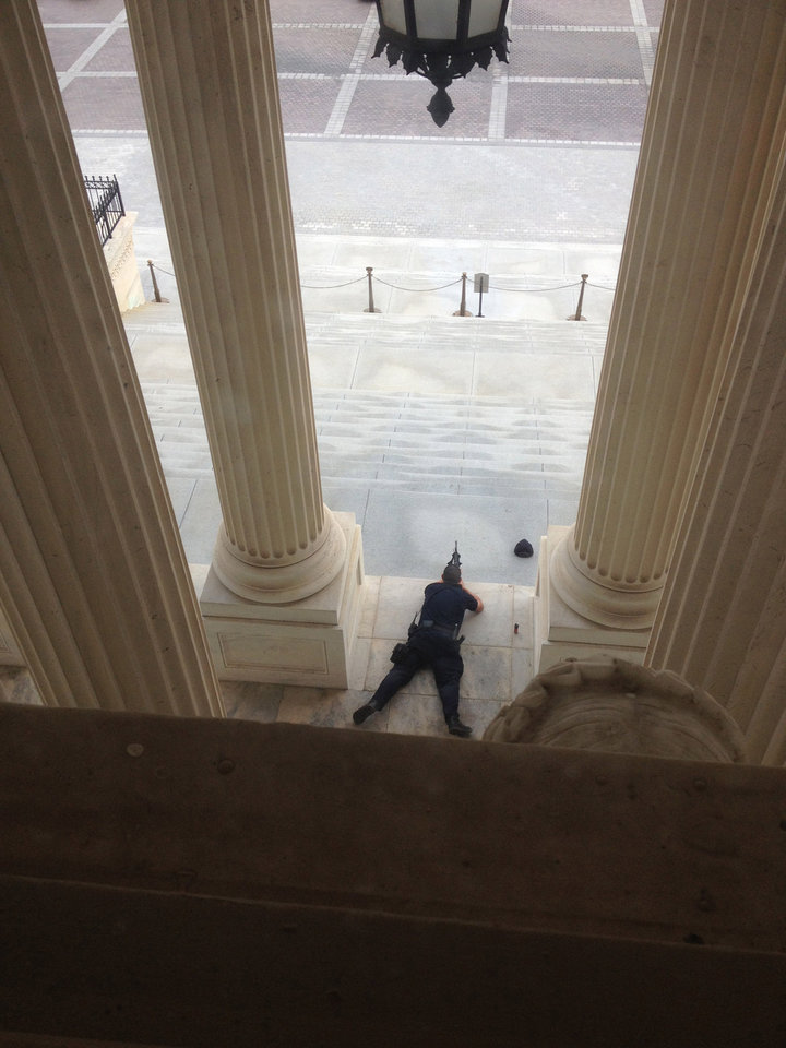Photo - A U.S. Capitol police officer lies on the steps of the Senate with a gun drawn in response to a report of shots fired Thursday, Oct. 3, 2012. A police officer was reported injured after gunshots at the U.S. Capitol. They locked down the entire complex, at least temporarily derailing debate over how to end a government shutdown. (AP Photo/The Tampa Bay Times, Alex Leary) TAMPA OUT; CITRUS COUNTY OUT; PORT CHARLOTTE OUT; BROOKSVILLE HERNANDO OUT; USA TODAY OUT; MAGS OUT