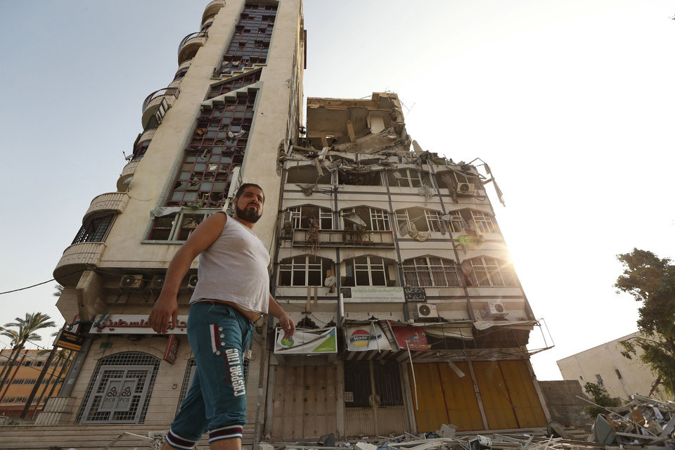 Photo - Palestinians inspect the damage of the Al-Shalam (Peace) tower, destroyed by an overnight Israeli strike, in Gaza City, Tuesday, July 22, 2014. A high-level attempt by the U.N. chief and the U.S. secretary of state to end deadly Israel-Hamas fighting was off to a rough start Monday: Gaza's Hamas rulers signaled they won't agree to an unconditional cease-fire, Israel's prime minister said he'll do whatever is necessary to keep Israelis safe from Hamas attacks. Gaza health officials say hundreds Palestinians have died since the beginning of Israel's campaign in the Gaza Strip since the ground operation began Thursday. (AP Photo/Lefteris Pitarakis)