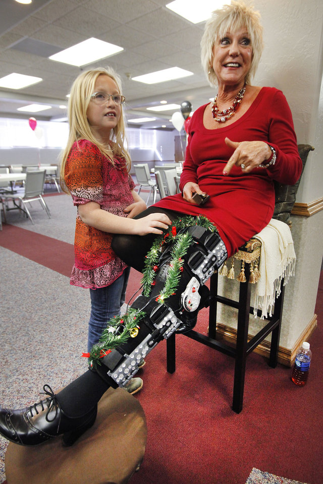 "Photo - Mesa Meadows, 10, talks with her aunt, City Clerk Nancy Nichols, about her ""blinged out"" splint at her retirement party. She is retiring after 28 years with the city of Edmond. PHOTO BY DAVID MCDANIEL, THE OKLAHOMAN"