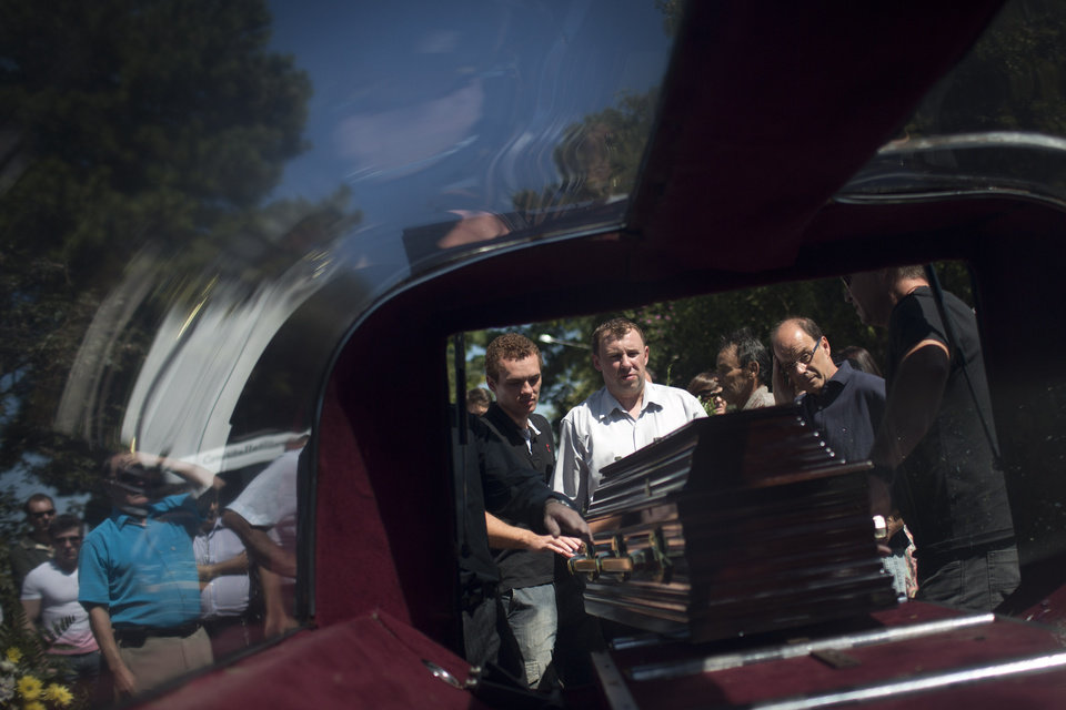 Photo - Relatives and friends remove from a hearse the coffin carrying the remains of a person who died in a nightclub fire as they arrive to a cemetery for burials in Santa Maria, Brazil, Monday, Jan. 28, 2013. A fast-moving fire roared through the crowded, windowless Kiss nightclub in this southern Brazilian city early Sunday, killing more than 230 people. Many of the victims were under 20 years old, including some minors. (AP Photo/Felipe Dana)