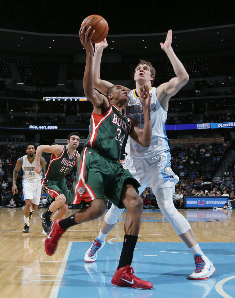 Photo - Milwaukee Bucks forward Giannis Antetokounmpo, front, of Greece, has his shot blocked by Denver Nuggets center Timofey Mozgov, of Russia, in the first quarter of an NBA basketball game in Denver, Wednesday, Feb. 5, 2014. (AP Photo/David Zalubowski)