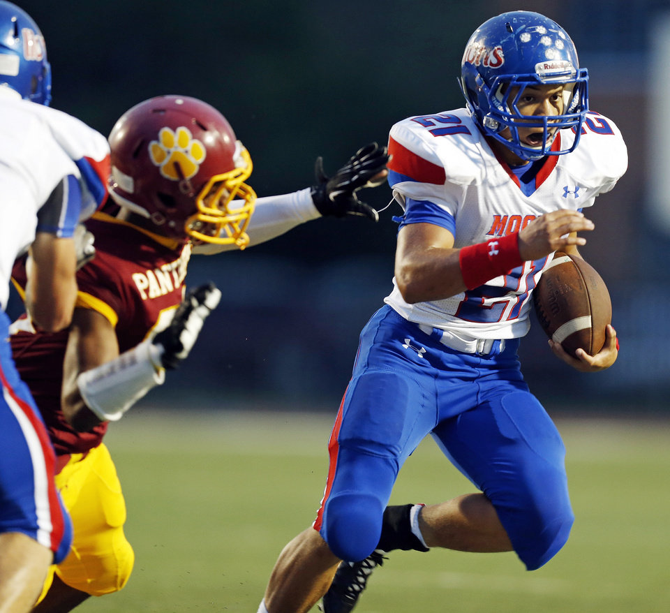 Moore's Ryan Lujan (21) escapes from a Putnam City North defender during a high school football game between Putnam City North and Moore at Putnam City Stadium in Oklahoma City, Thursday, Sept. 27, 2012. Photo by Nate Billings, The Oklahoman
