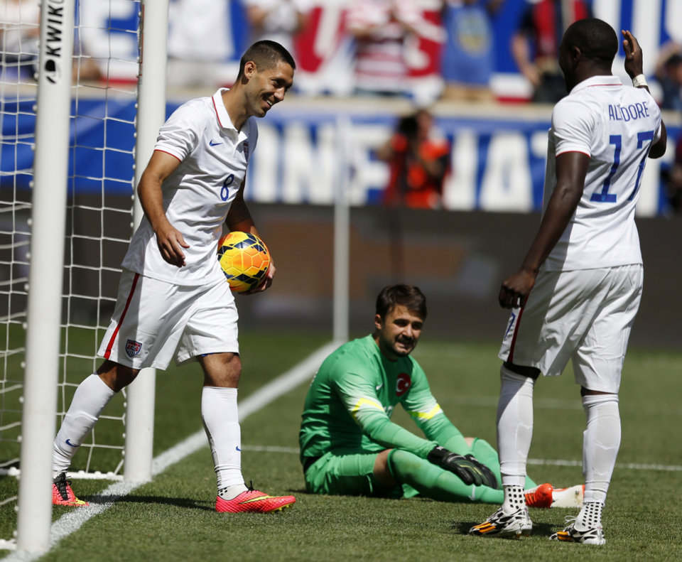 Photo - United States' Clint Dempsey, left, celebrates with teammate Jozy Altidore, right, after scoring a goal onTurkey goalkeeper Onur Recep Kivrak, center, in the second half of an international soccer friendly, Sunday, June 1, 2014, in Harrison, N.J. The U.S. won 2-1. (AP Photo/Julio Cortez)