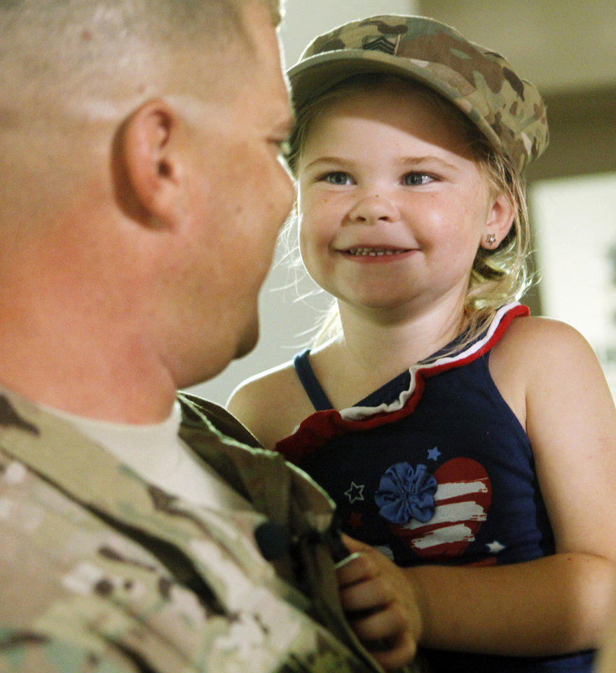 Photo - Four-year-old Alexis Bellar wears the hat of her father, Staff sgt. Jason Bellar, after he surprised his family with a return home during a minor league baseball game between the Oklahoma City Redhawks and the New Orleans Zephyrs at Chickasaw Bricktown Ballpark on July 8, 2014. Photo by KT King/The Oklahoman