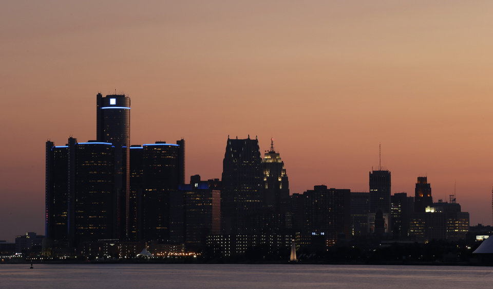 Photo - The sun sets on Detroit, Thursday, July 18, 2013. State-appointed emergency manager Kevyn Orr asked a federal judge for permission to place Detroit into Chapter 9 bankruptcy protection Thursday. (AP Photo/Paul Sancya)