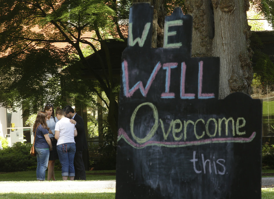 Photo - A group of people pray together near a sign on the Seattle Pacific University campus that reads