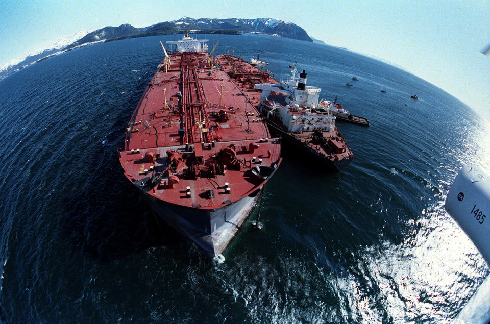 Photo - FILE - In this April 4, 1989, file photo, the grounded tanker Exxon Valdez, left, unloads oil onto a smaller tanker, San Francisco, as efforts to re-float the ship continue on Prince William Sound, 25 miles from Valdez, Alaska. The 987-foot tanker, carrying 53 million gallons of crude, struck Bligh Reef at 12:04 a.m. on March 24, 1989, and within hours unleashed an estimated 10.8 million gallons of thick, toxic crude oil into the water. Storms and currents then smeared it over 1,300 miles of shoreline. Twenty five years later, the region, its people and its wildfire are still recovering. (AP Photo, File)