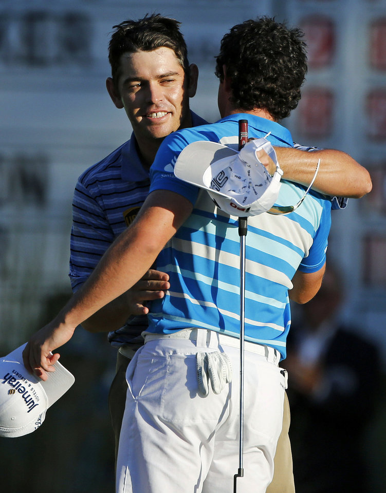 Photo -   Louis Oosthuizen, left, of South Africa, hugs Rory McIlroy, right, of Northern Ireland, after McIlroy won the Deutsche Bank Championship PGA golf tournament at TPC Boston in Norton, Mass., Monday, Sept. 3, 2012. Oosthuizen finished second. (AP Photo/Michael Dwyer)