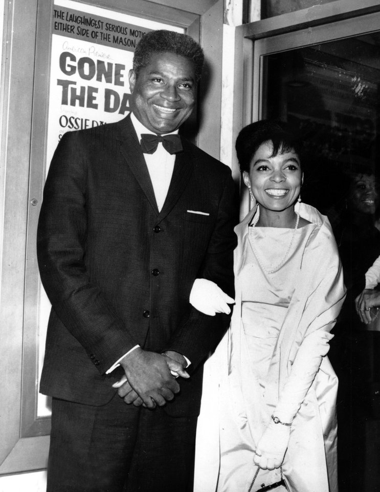 Photo - FILE - In this Sept. 23, 1963 file photo, actors Ossie Davis, left, and Ruby Dee pose in front of the movie poster at the opening night gala of their film