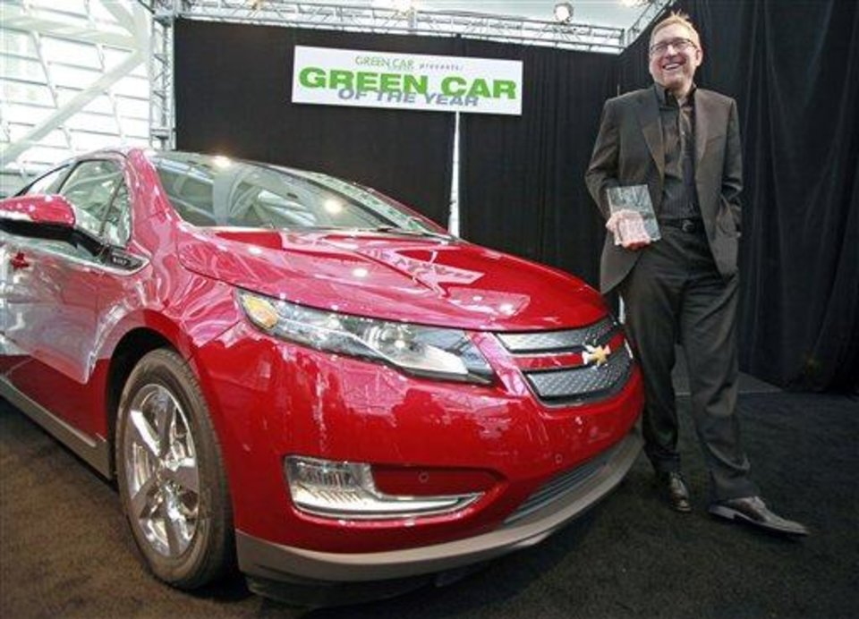 Joel Ewanick, General Motors Co. vice president for U.S. Marketing, holds the award won by the Chevy Volt as 2011 Green Car of the Year, presented by Green Car Journal, at the L.A. Auto Show Thursday, Nov. 18, 2010. (AP Photo/Reed Saxon)