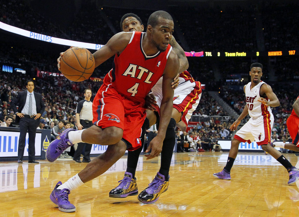 Photo - Atlanta Hawks' Paul Millsap (4) drives to the basket in front of Miami Heat power forward Udonis Haslem (40) in the third period of an NBA basketball game in Atlanta, Monday, Jan. 20, 2014. (AP Photo/Todd Kirkland)