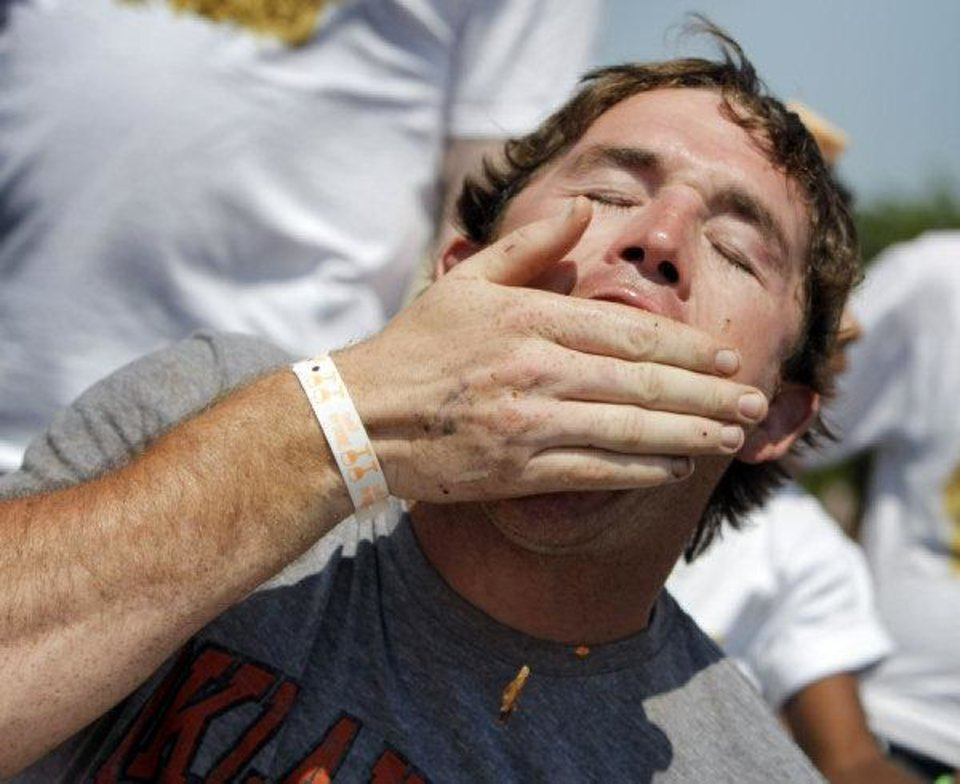 Photo - Ryan Lassley of Yale, Okla., stuffs his face during a bacon eating contest at Baconalia 2010, a bacon festival, in Enid, Okla., Saturday, August 28, 2010. Photo by Nate Billings, The Oklahoman ORG XMIT: KOD