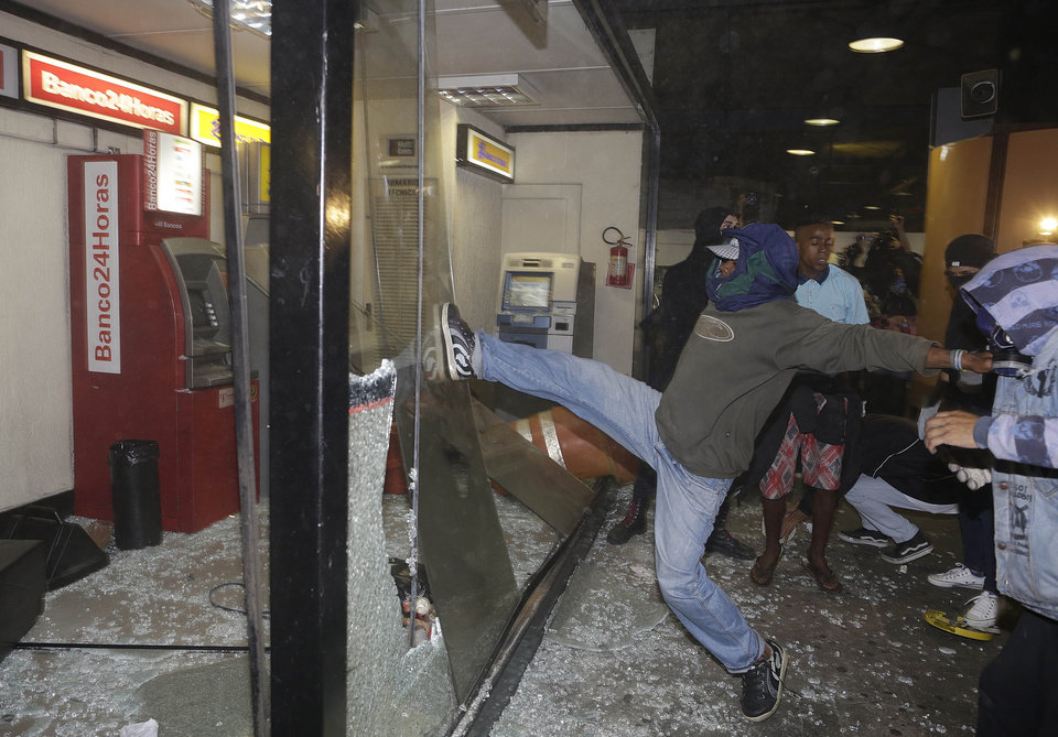 Photo - Black Bloc anarchists break windows near cash machines inside a bus terminal during a protest against Sao Paulo's Governor Geraldo Alckmin in Sao Paulo, Brazil, Friday, Oct. 25, 2013. Protesters are demanding a free public transportation system. (AP Photo/Andre Penner)