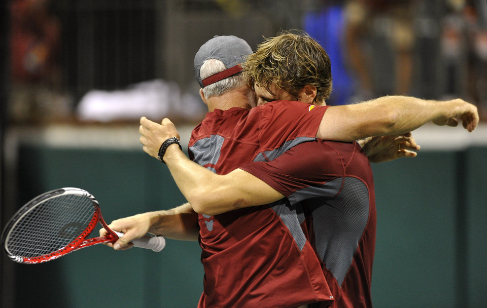 Photo - Southern California's Max de Vroome, right, hugs coach Peter Smith after they defeated Oklahoma's Andrew Harris to take the NCAA Division I men's team tennis title, Tuesday, May 20, 2014, in Athens, Ga. (AP Photo/David Tulis)