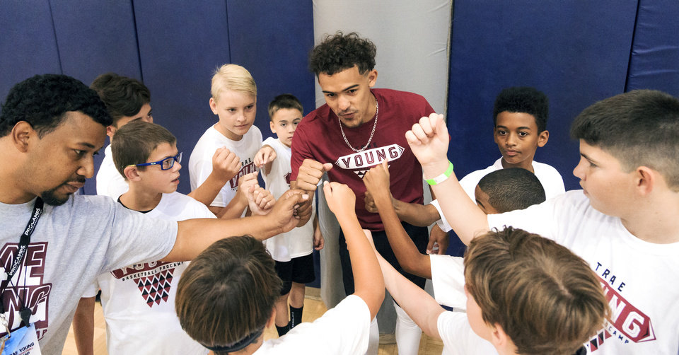 Photo -  Trae Young huddles up with a team as he works with campers on drills during the Trae Young Basketball Pro Camp at the University of Oklahoma's Sarkeys Fitness Center in Norman on Wednesday. [PHOTO BY CHRIS LANDSBERGER]