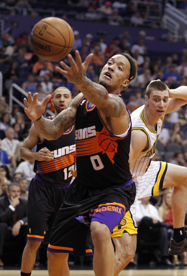 Photo - Phoenix Suns forward Michael Beasley, center, struggles to gain control of a ball before it lands out of bounds as Suns guard Kendall Marshall, left rear, and Indiana Pacers forward Tyler Hansbrough, right rear, look on during the first half of an NBA basketball game, Saturday, March 30, 21013, in Phoenix. (AP Photo/Paul Connors)
