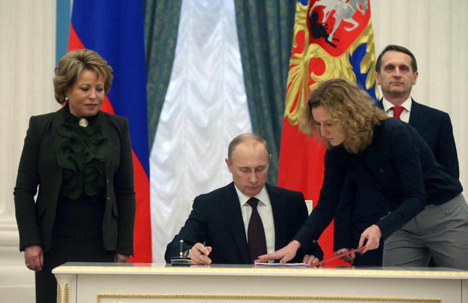 Photo - Russian President Vladimir Putin signs bills making Crimea part of Russia in the Kremlin in Moscow, Friday, March 21, 2014. President Vladimir Putin completed the annexation of Crimea on Friday, signing the peninsula into Russia at nearly the same time his Ukrainian counterpart sealed a deal pulling his country closer into Europe's orbit. At left is Upper House Speaker Valentina Matviyenko, at right back is Lower House Speaker Sergei Naryshkin. (AP Photo/Sergei Chirikov, Pool)