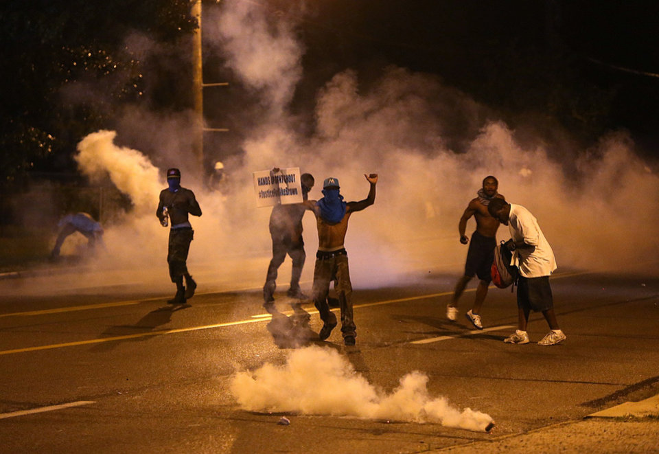 Photo - People protest as tear gas canisters detonate around them on Wednesday, Aug. 13, 2014, in Ferguson, Mo. Protests in the St. Louis suburb rocked by racial unrest since a white police officer shot an unarmed black teenager to death turned violent Wednesday night, with people lobbing molotov cocktails at police who responded with smoke bombs and tear gas to disperse the crowd. (AP Photo/St. Louis Post-Dispatch, Chris Lee)