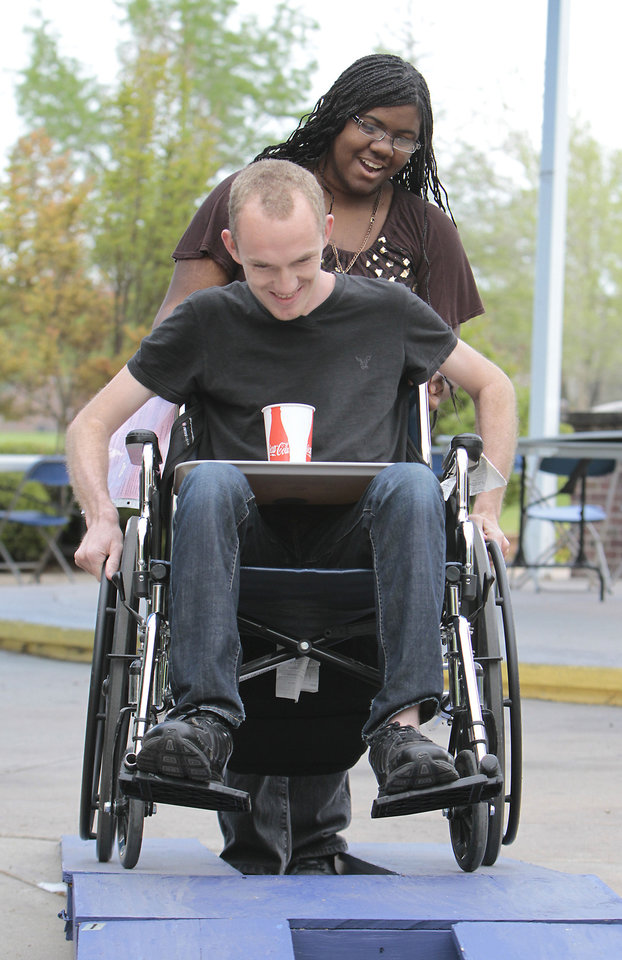 Volunteer Clea'rissa Bobo helps Joiner Darrell Potter navigate a wheelchair through an obstacle course with a cup of water on a tray as part of disability awareness week on the University of Central Oklahoma campus.