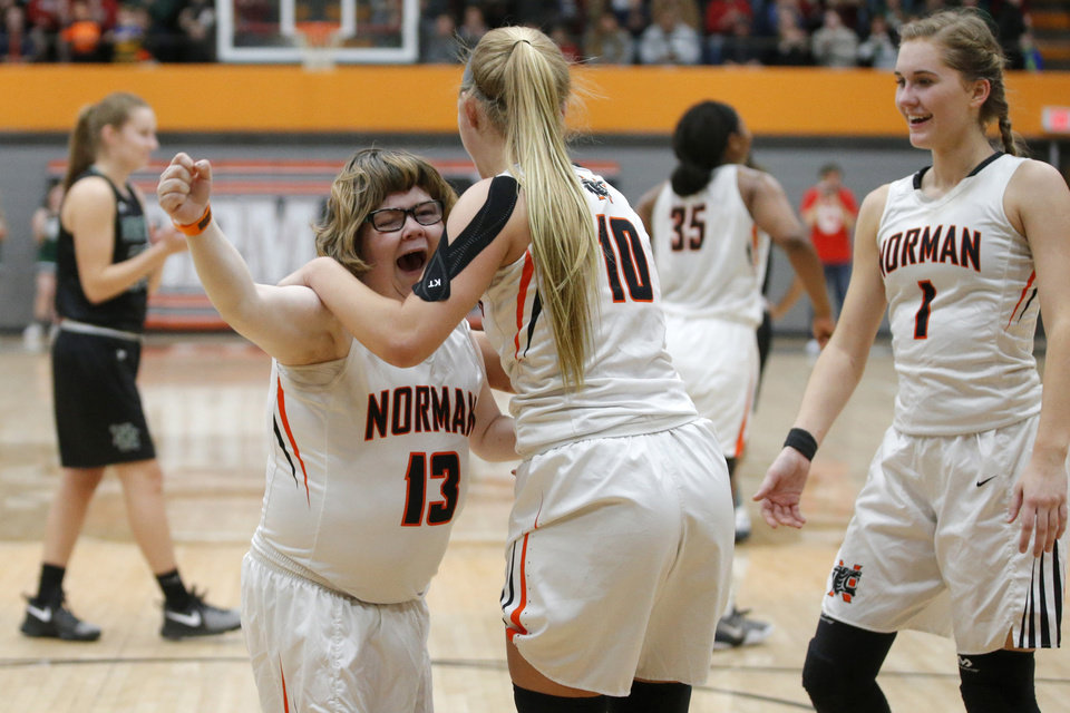 Photo - Norman's Lainy Fredrickson, left,  celebrates with teammate Brennan Hockett and Turner Mattingly after making a basket during a girls basketball game at Norman High School, Friday, Feb. 3, 2017. Photo by Bryan Terry, The Oklahoman
