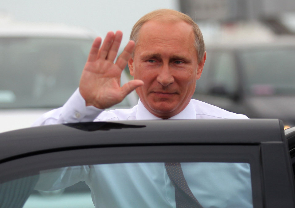 Photo - Russian President Vladimir Putin waves on his arrival in Minsk, Belarus, Tuesday, Aug. 26, 2014. The presidents of Russia and Ukraine sat down for talks Tuesday, meeting face-to-face for the first time since June on the fighting that has engulfed Ukraine's separatist east. (AP Photo/Dmitry Brushko)