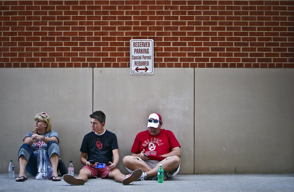 Marsha, Dalton and Jeramy Rhoden, from left, find a cool spot in the shade as they wait for the gates to open for the college football game between the University of Oklahoma Sooners (OU) and the Tulsa University Hurricanes (TU) at the Gaylord Family-Memorial Stadium on Saturday, Sept. 3, 2011, in Norman, Okla. Photo by Chris Landsberger, The Oklahoman
