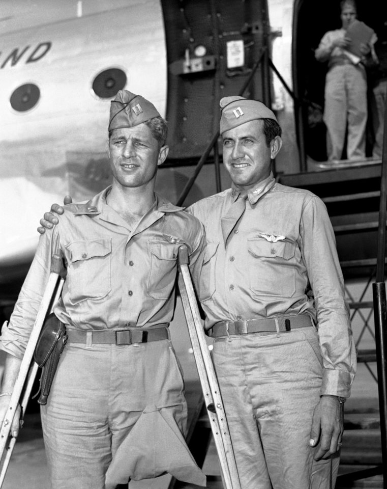 Photo - FILE - In a Oct. 3, 1945 file photo, Capt. Louis Zamperini (right), Torrence, Calif., former track star, who was adrift 47 days in Pacific after bombing mission against the Japanese and presumed dead, stands with his Pal, Capt. Fred Garrett, Riverside, Calif., upon  their arrival at Hamilton Field, Calif. Both were prisoners of war. Zamperini, a U.S. Olympic distance runner and World War II veteran who survived 47 days on a raft in the Pacific after his bomber crashed, then endured two years in Japanese prison camps, died Wednesday, July 2, 2014, according to Universal Pictures studio spokesman Michael Moses. He was 97. (AP Photo/PCS, File)