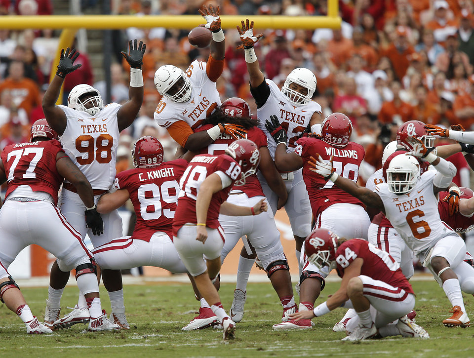 Photo - The Texas defense tries to block a field goal by Oklahoma's Michael Hunnicutt (18) during the college football game between the University of Oklahoma Sooners (OU) and the University of Texas Longhorns (UT) during the Red River Showdown at the Cotton bowl in Dallas, Texas on Saturday, Oct. 11, 2014. Photo by Chris Landsberger, The Oklahoman