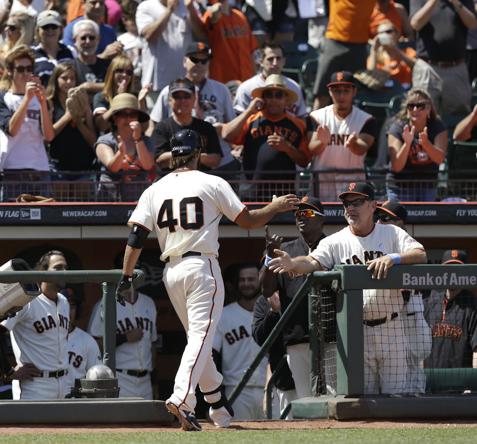 Photo - San Francisco Giants' Madison Bumgarner (40) is congratulated by manager Bruce Bochy, right, after hitting a solo home run off of Colorado Rockies pitcher Franklin Morales during the fifth inning of a baseball game in San Francisco, Sunday, June 15, 2014. (AP Photo/Jeff Chiu)