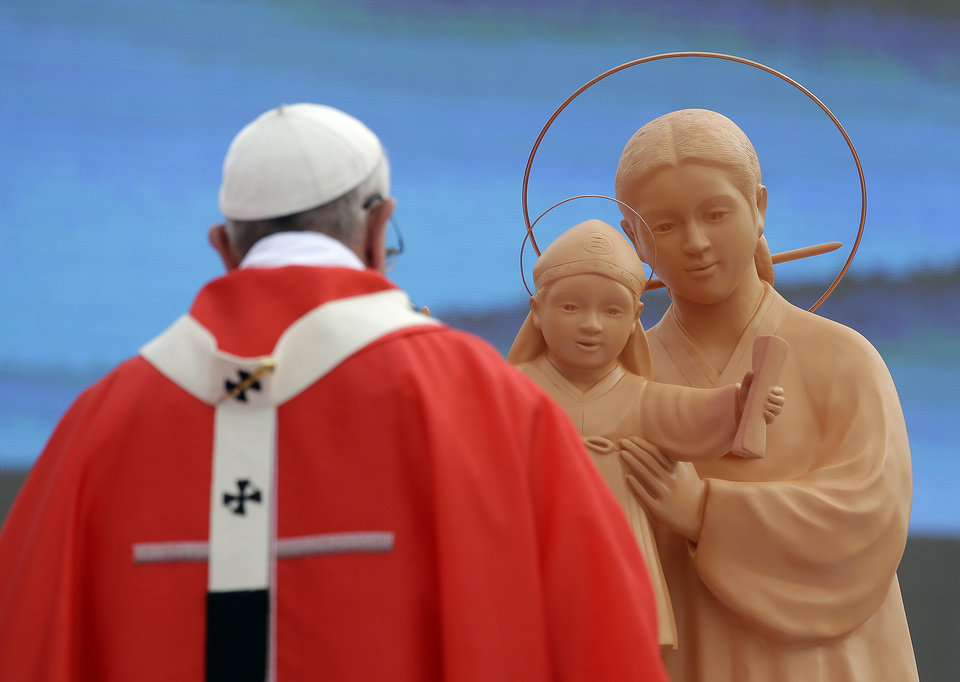 Photo - Pope Francis stands in front of a statue of Mary and Baby Jesus as he celebrates a mass and the beatification of Paul Yun ji-Chung and 123 martyr companions at Gwanghwamun Gate in Seoul, South Korea, Saturday, Aug. 16, 2014. Paul Yun Ji-Chung who was born in 1759 was among the earliest Catholics on the peninsula. (AP Photo/Gregorio Borgia)