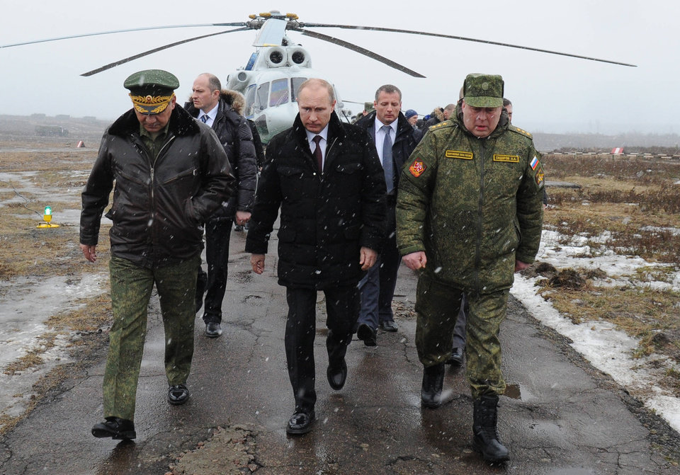 Photo - Russian President Vladimir Putin, center, and Defense Minister Sergei Shoigu, left, and the commander of the Western Military District Anatoly Sidorov, right, walk upon arrival to watch military exercise near St.Petersburg, Russia, Monday, March 3, 2014. Putin has sought and quickly got the Russian parliament's permission to use the Russian military in Ukraine.(AP Photo/RIA-Novosti, Mikhail Klimentyev, Presidential Press Service)