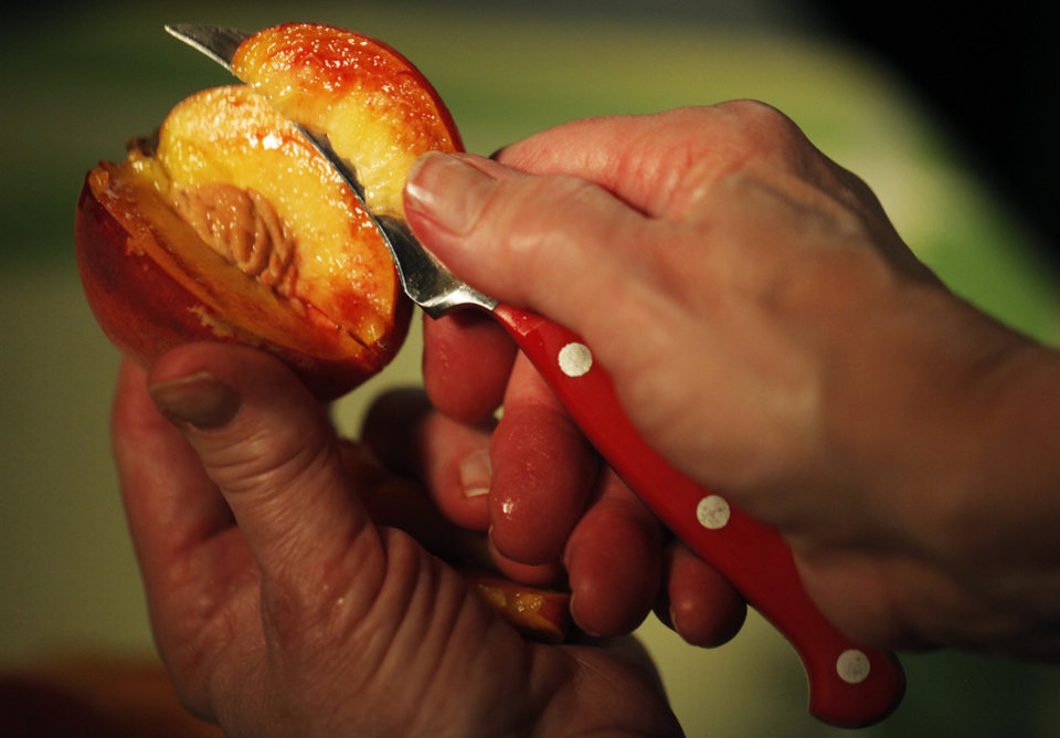 Photo - FOOD: Slicing open a peach that is locally grown in Oklahoma in the studio on July 3, 2013. Photo by K.T. KING, The Oklahoman