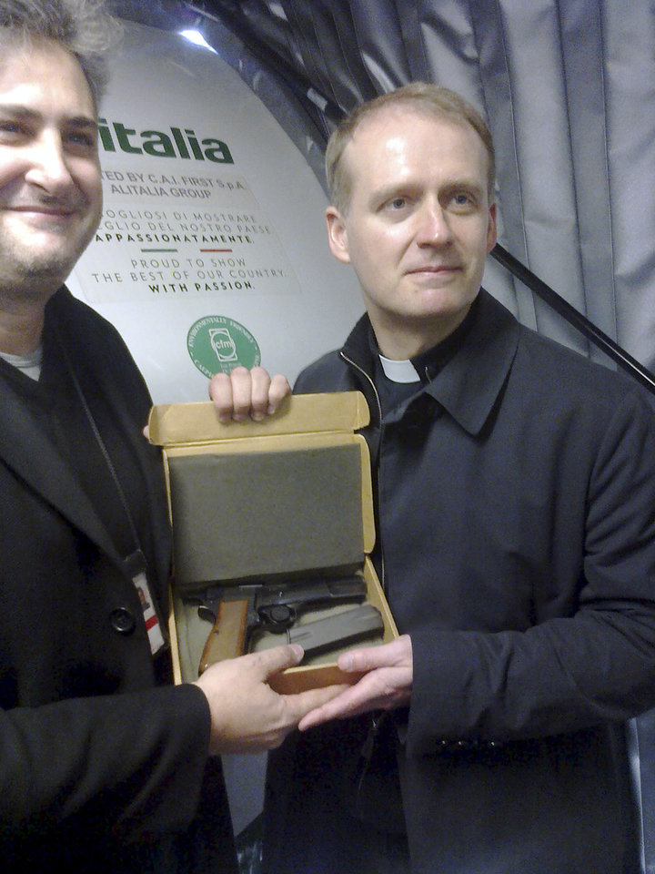 Photo - In this photo provided by Alitalia, Monsignor Dariusz Ras, right, shows the Browning HP 9mm handgun used to shoot Pope John Paul II in the abdomen in St. Peter's Square at the Vatican, on May 13, 1981. Alitalia Flight 488 landed in Krakow, Poland on Tuesday, March 18, 2014 with some very special cargo on board: The gun used to shoot Pope John Paul II. Monsignor Dariusz Ras, the Polish priest who runs the John Paul II museum in the late pope's childhood home in Wadowice, transported the pistol from Rome to Poland for the museum's upcoming exhibit in honor of John Paul's April 27 canonization, Alitalia said. Mehmet Ali Agca used the Browning HP 9mm handgun to shoot John Paul in the abdomen in St. Peter's Square on May 13, 1981. The pope spent nearly three weeks in the hospital recovering. (AP Photo/Alitalia)