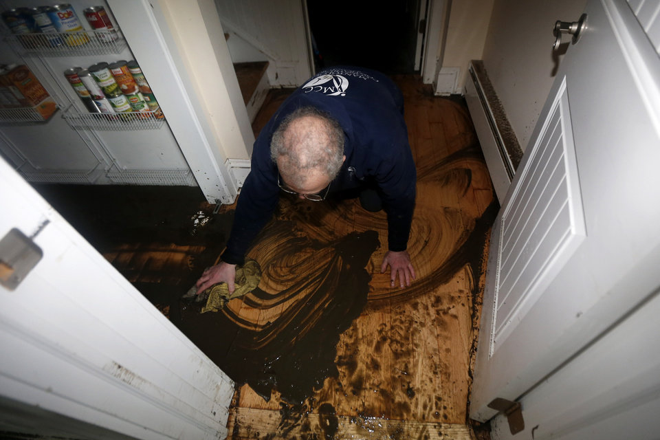 Photo - Calvin Colabella uses a mop to clean up mud from the first floor of his home, which was flooded in the wake of Superstorm Sandy, Thursday, Nov. 1, 2012, in Brick, N.J. Sandy, the storm that made landfall Monday, caused multiple fatalities, halted mass transit and cut power to more than 6 million homes and businesses. (AP Photo/Julio Cortez) ORG XMIT: NJJC108
