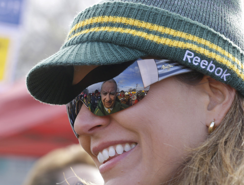 Tommy Thompson, republican candidate for U.S. senate and former Gov. of Wis, is reflected in a woman's glasses while tailgating at Lambeau Field before the Green Bay Packers and Arizona Cardinals NFL football game Sunday, Nov. 4, 2012, in Green Bay, Wis. (AP Photo/Jeffrey Phelps)