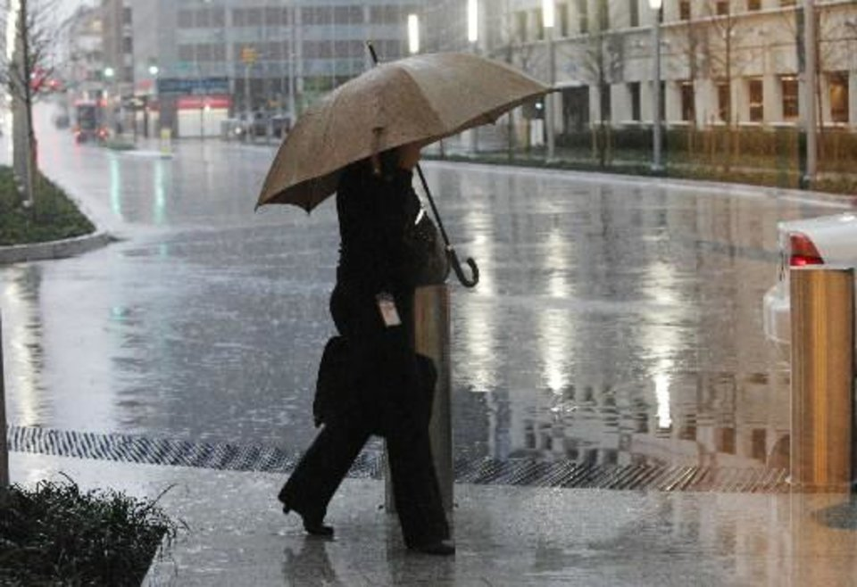 A pedestrian hurries to work in the pouring rain as thunderstorms move through near Harvey and Park in downtown Oklahoma City Monday, March 19, 2012. Photo by Paul B. Southerland, The Oklahoman