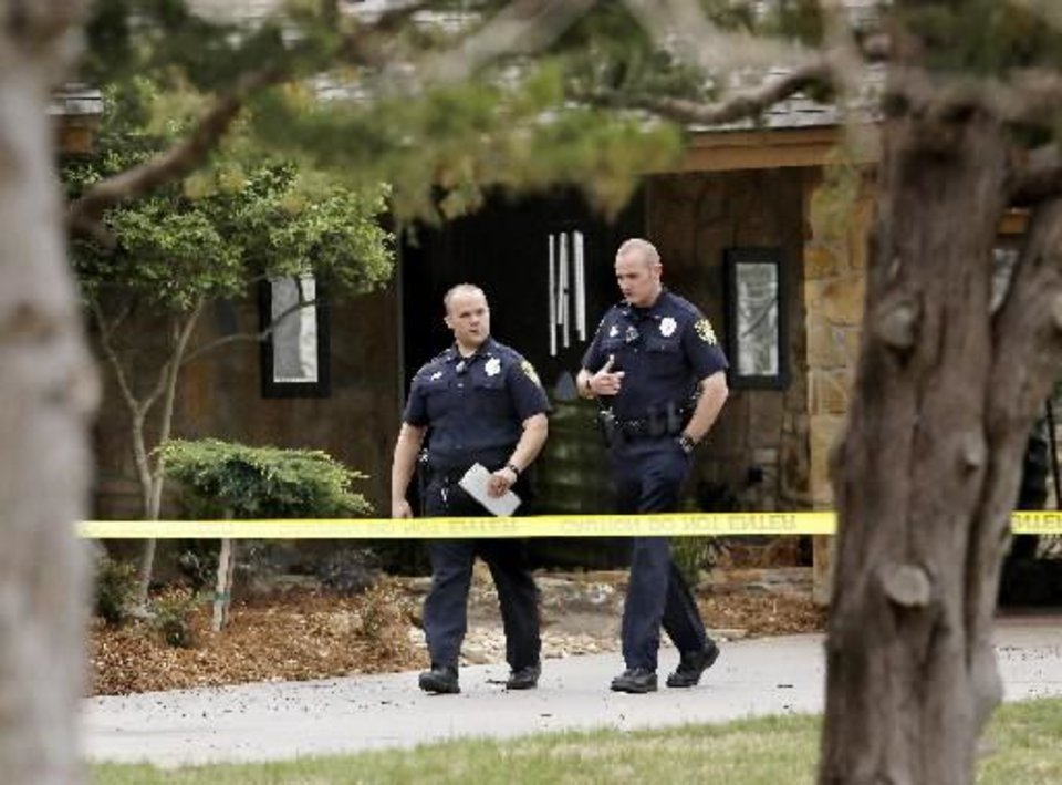 Photo - Police officers walk behind crime scene tape in front of home where worm was found dead inside. Shawnee police investigate the scene of a pre-dawn homicide in an upscale neighborhood in northeast Shawnee Thursday, March 21, 2013. Police confirmed that Cathy Byus was killed in a domestic-related homicide inside her home at 27 Bella Vista Vista Lane. Photo by Jim Beckel