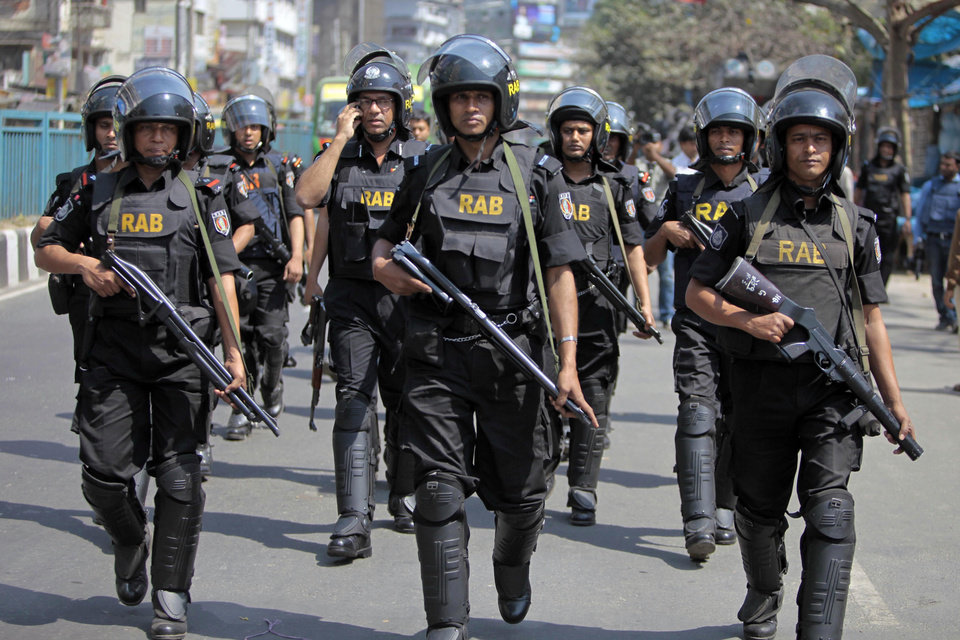 Bangladeshi security personnel patrol in front of Baitul Mukarram mosque in Dhaka, Bangladesh, Friday, March 1, 2013. Protesters clashed with police for a second day Friday as the death toll rose to at least 44 in clashes triggered by a death sentence given to Delwar Hossain Sayedee, one of the top leaders of the country's largest Islamic party Jamaat-e-Islami, for crimes linked to Bangladesh's 1971 independence war, police said. (AP Photo/A.M. Ahad)
