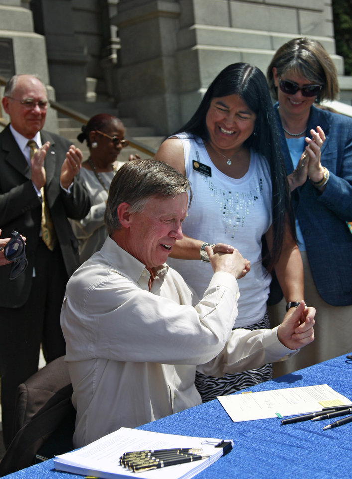Photo - Colorado Governor John Hickenlooper  shakes hands with Medicaid bill sponsor, state senator Irene Aguilar, MD, as Hickenlooper signs into law an expansion of Medicaid eligibility that's expected to add 160,000 adults to public health care assistance, at the state Capitol, in Denver, Monday May 13, 2013. The expansion is part of the federal health care overhaul. (AP Photo/Brennan Linsley)