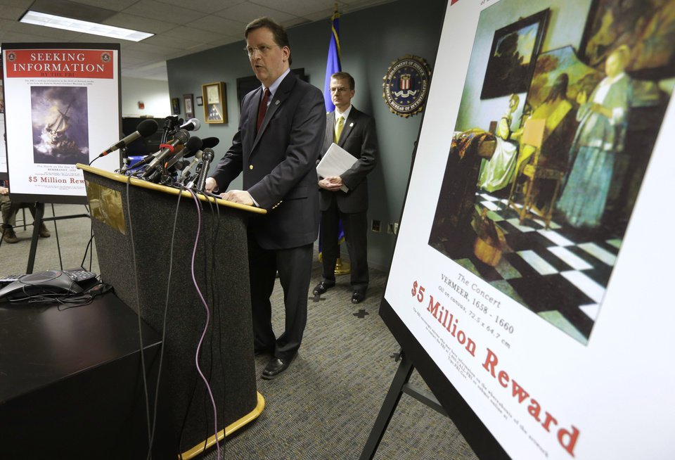 Photo - Anthony Amore, chief of security at the Gardner Museum, center, stands next to a poster that shows an image of a Vermeer painting and lists a reward, right, while facing reporters during a news conference at FBI headquarters in Boston, Monday, March 18, 2013. The FBI believes it knows the identities of the thieves who stole art valued at up to $500 million from Boston's Isabella Stewart Gardner Museum more than two decades ago. (AP Photo/Steven Senne)