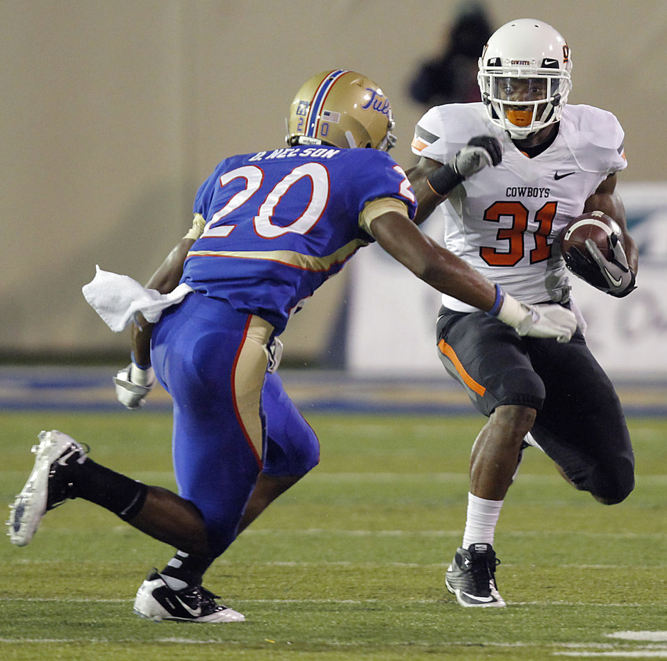 Oklahoma State's Jeremy Smith (31) looks for running room past Tulsa's Marco Nelson (20) during a college football game between the Oklahoma State University Cowboys and the University of Tulsa Golden Hurricane at H.A. Chapman Stadium in Tulsa, Okla., Sunday, Sept. 18, 2011. Photo by Chris Landsberger, The Oklahoman