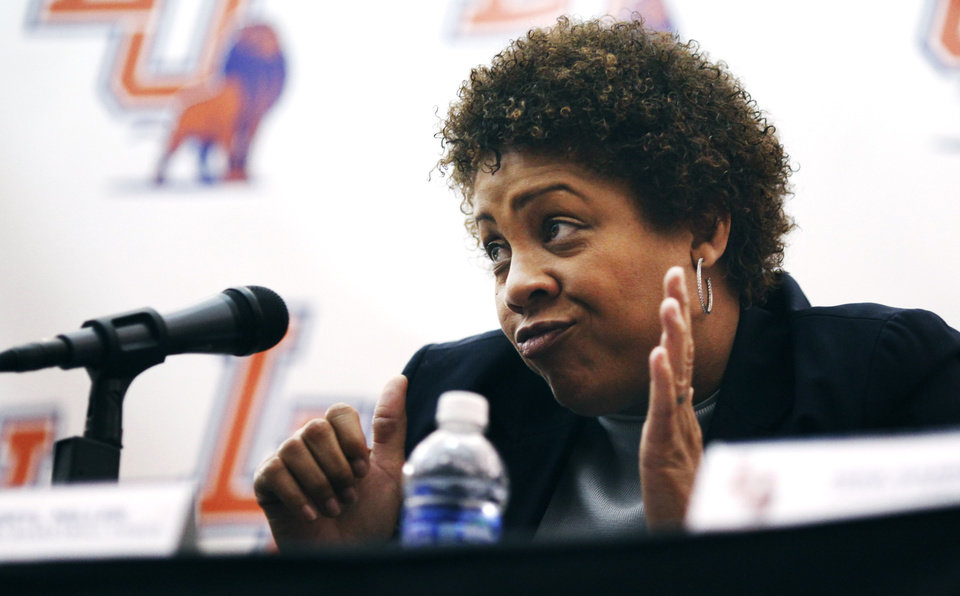 Photo - Women's basketball great Cheryl Miller dances while sitting in her seat at a press conference where she was introduced as the head coach of Langston's women's basketball program on Tuesday, April 29, 2014 Photo by KT King, The Oklahoman