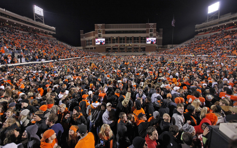 Photo - Fans storm the field to celebrate the Cowboys' 44-10 win over Oklahoma during the Bedlam college football game between the Oklahoma State University Cowboys (OSU) and the University of Oklahoma Sooners (OU) at Boone Pickens Stadium in Stillwater, Okla., Saturday, Dec. 3, 2011. Photo by Chris Landsberger, The Oklahoman