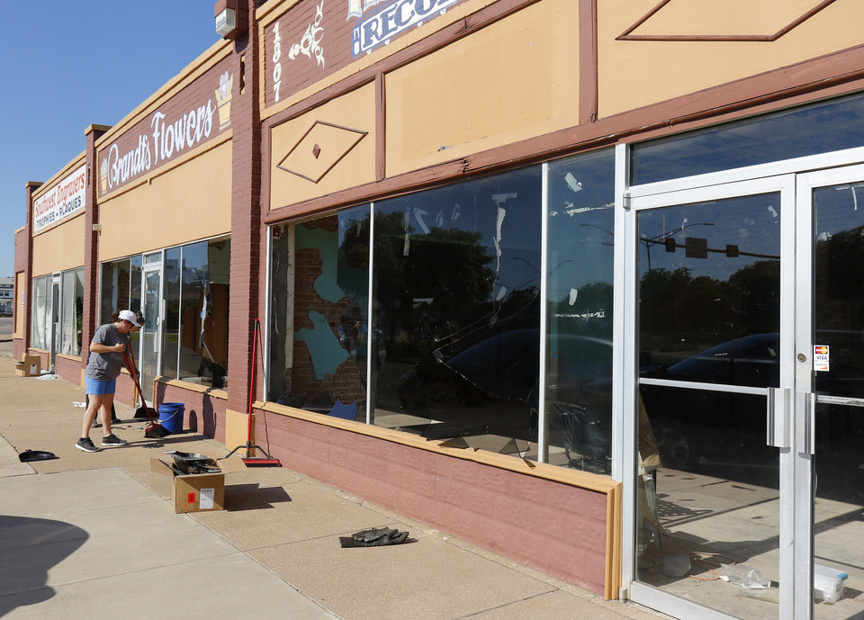 Photo - Angie Mendez and Deette Hankins sweep up broken glass in front of The Saucee Sicilian's location they are building on Classen Blvd. Damage from Saturday night protest in downtown Oklahoma City, Sunday, May 31, 2020. [Doug Hoke/The Oklahoman]